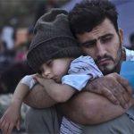 Refugiado sírio acalentando o filho
